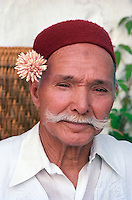 """Tunisia, Sidi Bou Said.  Coffee Shop Owner, Hajj Omar, wearing a Chechia, the Traditional Tunisian Hat, and a Jasmine Sprig behind the Ear.  The grayish spot (""""zabiba"""") in the upper middle of his forehead is a light callus. This often marks a faithful observer of the Muslim prayers five times a day, in which the forehead gently comes in contact with the prayer rug as the worshipper goes through his prostrations."""