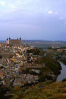 View of city from east of Tajo river. Large building at top of hill is El Alcazar. Toledo Castilla-La Mancha Spain.