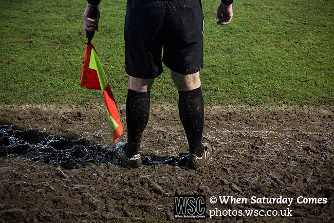 Belper Town v Gresley, 28/01/2014. Christchurch meadow, Northern Premier League. The referee's assistant standing in the mud during the second-half of Belper Town's match against Gresley, in a Northern Premier League, first division south fixture at Christchurch meadow. The home side have played at their current ground since the club was reformed in 1951. Belper won this fixture against their local Derbyshire rivals by 4 goals to 1 watched by a crowd of 165 spectators. Photo by Colin McPherson.