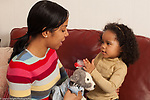 3 year old girl with mother talking pretend play brushing fur of stuffed toy animal dog