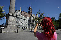 Montreal quebec CANADA - july 02, 2012 - MODEL RELEASED ILLUSTRATION - adult female walking around in Old-Montreal taking picture of the City Hall with her smart phone.