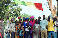 Mali. Province of Segou. Niono. October 16 2003. Worlwide food day. The crowd waits under the malian flag (green, yellow and red) for the arrival of the malian president Amadou Toumani Toure (ATT). The young boys are dressed with western clothes while the women wear the traditional malian suit, the Boubou. © 2003 Didier Ruef