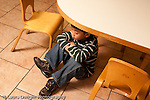 Preschool Headstart 3-5 year olds sad isolated boy sitting under child-size table in classroom at school horizontal