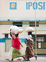 Women walk with supply bags balanced on their heads past the Post Office in Gisenyi, Rwanda