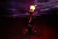 A man with his hat of flame rides on a bicycle at the Burning Man Festival. Elaborate, colorful and clever costumes are part of the annual weeklong fest held in Black Rock Desert, northwestern Nevada's Conservation area.  The counter-culture celebration focuses on art and self-expression.