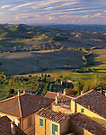 Tuscany, Italy:  Coloful buildings and tiled roofs of Montepulciano with the rolling hills of the countryside in the background