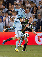 Julio Cesar (55)  and Roger Espinoza (15) of Sporting Kansas City collide with Andy Rose (25) of the Seattle Sounders during the game at Livestrong Sporting Park in Kansas City, Kansas.   Sporting Kansas City won the Lamar Hunt U.S. Open Cup on penalty kicks after tying the Seattle Sounders in overtime.