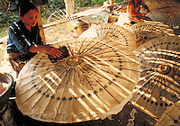 A woman applies decals to a paper umbrella. Chiang Mai, Thailand. Chiang Mai, Thailand.