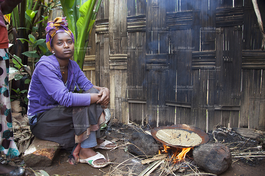 Ethiopia. Southern Nations, Nationalities, and Peoples' Region. Omo Valley. Hayzo Village. High altitude: 2800 meters. Dorze tribe. A young woman seated on a rock cooks on fire the ensete or false banana for a preparation of food dough and bread, called Kocho. The Dorze are a small ethnic group inhabiting the Gamo Gofa Zone who speak the Dorze language, an Omotic tongue. The Dorze are predominantly agriculturalists living in permanent villages. Ensete ventricosum, commonly known as the Ethiopian banana, Abyssinian banana, false banana, or ensete, is an herbaceous species of flowering plant in the genus Ensete of the banana family Musaceae. The Dorze numbered 40'000 reside in villages near the cities of Chencha and Arba Minch. Southern Nations, Nationalities, and Peoples' Region (often abbreviated as SNNPR) is one of the nine ethnic divisions of Ethiopia. 6.11.15 © 2015 Didier Ruef