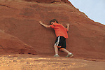 Boy rock climbing on slickrock in Arches National Park, Moab, Utah, USA. .  John offers private photo tours in Arches National Park and throughout Utah and Colorado. Year-round.
