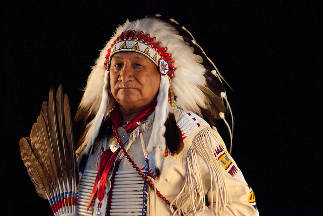 Jonas Grant (Ute/Navajo/Apache) dressed in eagle feather headdress warbonnet and deer skin jacket decorated with beadwork holds a dance fan next to a black background.
