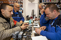 Switzerland. Geneva. Paquis neighborhood. Four police officers search a shop selling mobile phones ( new and second hand) looking for illegal business deals. The policemen control the serial numbers of each phone because they suspect the shop's owner of concealment activities. One of the police officers wear plain clotehs, the others a blue police uniform. A police officer (R) is wearing a ballistic vest, bulletproof vest or bullet-resistant vest which is an item of personal armor that helps absorb the impact from knives, firearm-fired projectiles and shrapnel from explosions, and is worn on the torso. Soft vests are made from many layers of woven or laminated fibers and can be capable of protecting the wearer from small-caliber handgun and shotgun projectiles. 20.03.12 © 2012 Didier Ruef..