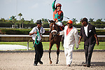Candy Coded Kisses with jockey Cecilio Penalba celebrate victory at odds of 24-1, in the Desert Vixen Division of the Florida Stallion Stakes of 2012 at Calder Race Course, Miami Gardens Florida. 07-28-2012. Arron Haggart/Eclipse Sportswire.