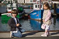 Europe/France/Aquitaine/64/Pyrénées-Atlantiques/Pays Basque/ Saint-Jean-de-Luz: Europe/France/Aquitaine/64/Pyrénées-Atlantiques/Pays Basque/ Saint-Jean-de-Luz: Enfants sur le port de pêche en fond les maisons de Ciboure. - Les enfants sont habillés par: Arsène  et les Pipelettes( Styliste: Chloé de Bailliencourt)AUTO N°:8001-AUTO N°:8002 [Non destiné à un usage publicitaire - Not intended for an advertising use]