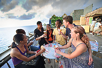 Montego Bay, Jamaica. Newlywed couple having drinks with friends at Margaritaville Bar. Jamaica Tourism.