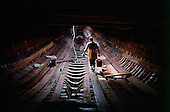 Sur, Oman<br /> July 2001<br /> <br /> A worker cleans between the wooden beams that supports the engine.