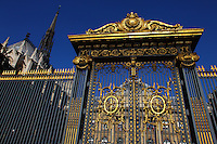 In the Ile de la Cité, a typical gilt fence and a majestic golden gate with the main court of the Palais de Justice (Justice Palace) of Paris on the background. This is the Cour de Mai (Court of May), surmounted by the top of the back of the Sainte Chapelle.
