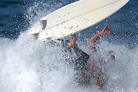 A male surfer wipes out during a competiton