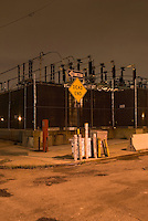 Urban Street Scene at Night, with electric power substation, sidewalk and street signs, in the Vinegar Hill neighborhood of Brooklyn, New York City, New York State, USA