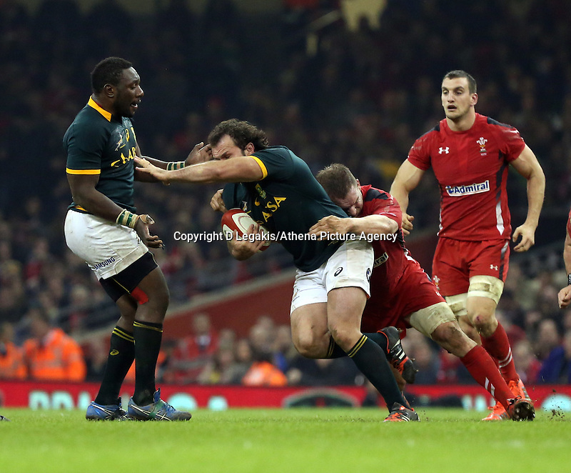 Pictured: Bismarck du Plessis of South Africa (with ball) is grabbed from behind by Gethin Jenkins of Wales Saturday 29 November 2014<br /> Re: Dove Men Series 2014 rugby, Wales v South Africa at the Millennium Stadium, Cardiff, south Wales, UK.