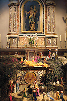 """Switzerland. Canton Tessin. Vira Gambarogno. The old town shows an exhibit of various Nativity scenes, illuminated at night for the Christmas holiday season. A Nativity Scene, may be used to describe any depiction of the Nativity of Jesus in art, but in the sense covered here, also called a crib or in North America and France a crèche (meaning """"crib"""" or """"manger"""" in French). It means a three-dimensional folk art depiction of the birth or birthplace of Jesus, either sculpted or using two-dimensional (cut-out) figures arranged in a three-dimensional setting. Christian nativity scenes, in two dimensions (drawings, paintings, icons, etc.) or three (sculpture or other three-dimensional crafts), usually show Jesus in a manger, Joseph and Mary in a barn (or cave) intended to accommodate farm animals. The scene includes the Magi or Three Wise Men, shepherds and sheep, angels, and the Star of Bethlehem. Church's altar. Sculture of the Vigin Mary and Jesus. © 2007 Didier Ruef"""