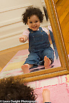 18 month old toddler girl looking at self in mirror recognizing self