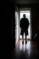 An elderly man stands in the doorway of his son's home where he now lives after his wife died and his health declined.