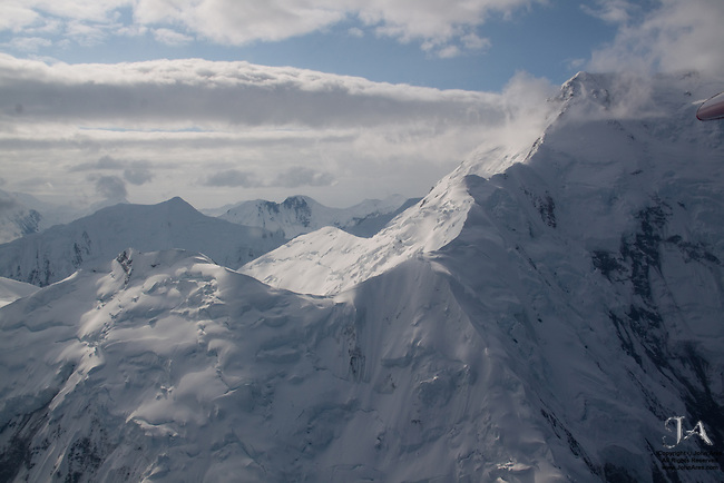 Aerial view of one of Mount Mckinley's eastern ridges in bright sun, with some clouds, near Wickersham Wall.