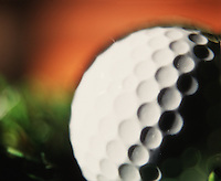 Close up detail of the dimples on a golf ball.