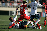 Oguchi Onyewu tackles the ball as China's Dong Fangzhuo and USA's DaMarcus Beasley close in. USA defeated China, 4-1, at Spartan Stadium in San Jose, Calif., on June 2, 2007.