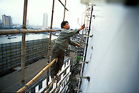 Migrant worker on Carlsberg neon sign on the Pearl River in Guangzhou, China..
