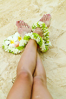Close up of womans feet with plumeria flowers, draped with flower lei