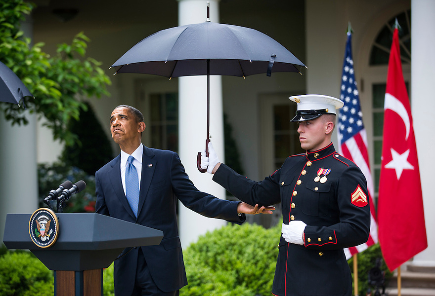 U.S. President Barack Obama checks to see if he still needs the umbrella held by a U.S. Marine to protect him from the rain during a joint news conference with Turkish Prime Minister Recep Tayyip Erdogan in the Rose Garden of the White House in Washington.