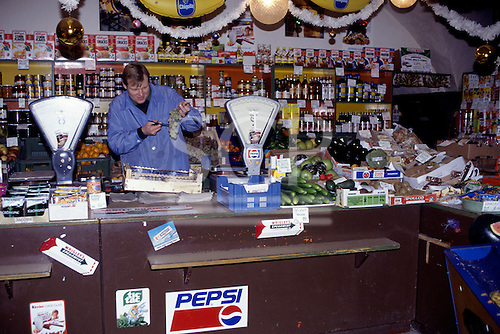 Prague, Czech Republic. Small grocers shop selling different goods - vegetables, drinks, cereals. Shopkeeper cutting a bunch of grapes.