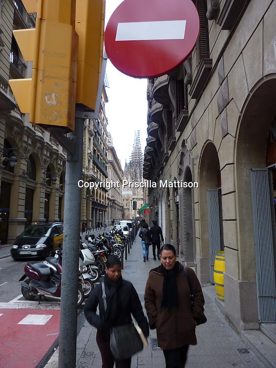 "Barcelona, Spain - January 29, 2011:  Two women walk towards a  ""no entry"" traffic sign."