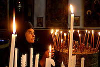 Christians in Bethlehem - A Christian nun lights votive candles in the Church of the Nativity, the traditional birthplace of Jesus in the West Bank town of Bethlehem. Photo by Quique Kierszenbaum