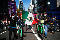 NEW YORK, NY - OCTOBER 15: Delivery workers carry a Mexican flag as they take part in a protest to stop thefts of their bikes at Times Square on October 15, 2020 in New York, At least 4,477 bicycles have been reported stolen with an increase of 27 percent from same period last year, according to the police. (Photo by Eduardo MunozAlvarez/VIEWpress)