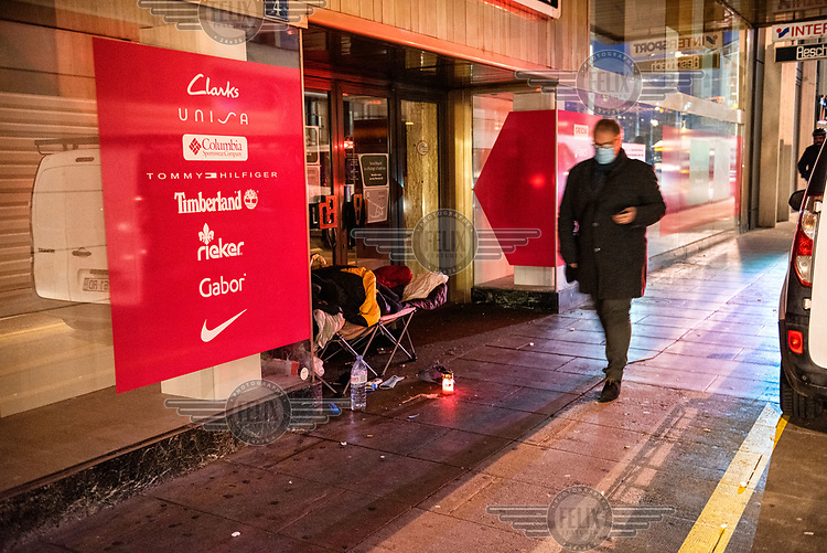 A commuter passes a homeless man sleeping on a camp bed outside a shop closed for renovations on the Rue du Rhone.
