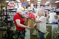 Dotted Pig owner Sherry Puttkammer (right) hands goods to Meza Harris of Rogers (left), Friday, September 10, 2021 at the Dotted Pig in Rogers. Check out nwaonline.com/210912Daily/ for today's photo gallery. <br /> (NWA Democrat-Gazette/Charlie Kaijo)