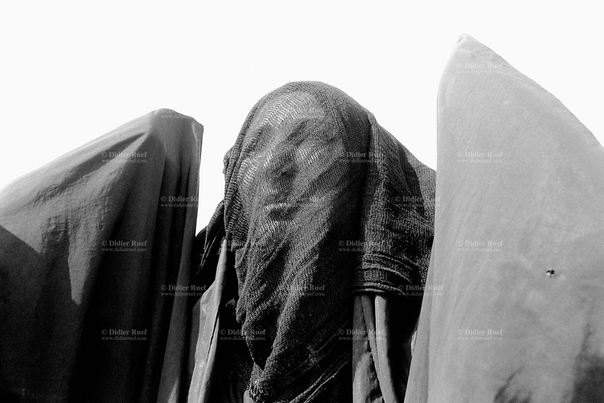 """Iraq. Basrah. Al Fao neighbourhood. A moslem woman, dressed with the abaya, looks at the procession, the celebration and the religious commemoration of the day of Ashura. Muharram is a month of remembrance that is often considered synonymous with the event of Ashura. Ashura, which literally means the """"Tenth"""" in Arabic, refers to the tenth day of Muharram. It is well-known because of historical significance and mourning for the martyrdom of Hussein ibn Ali, the grandson of Muhammad. Shi'a Muslims start the mourning from the 1st night of Muharram and continue for two months and eight days. However the last days are the most important since these were the days where Hussein and his family and followers were killed in the Battle of Karbala which took place on Muharram 10, in the year 61 of the Islamic calendar (October 10, 680). Muharam's month is considerated as one of the most important feast for the Shiism branch of Islam. Shia Islam is the second largest denomination of Islam. The followers of Shia Islam are called Shi'ites or Shias. Basra ( in arabic Al Ba"""