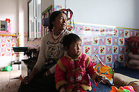 A Tibetan woman and hr grandchild in their home on the Tibetan Plateau, in western China. Relocation communities been created to house nomadic herders moved from the highland grasslands. The nomads have been blamed for contributing to the deterioration of the grasslands, so have been moved, sometimes forcibly, into newly built towns that can be found across the plateau.