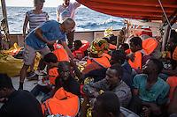 Sea Watch-2.<br /> Die Sea Watch-2 bei ihrer 13. SAR-Mission vor der libyschen Kueste.<br /> Im Bild: Die Sea Watch-2 hat knapp 200 Menschen an Bord aufgenommen. Sie muessen auf dem Deck ausharren, bis ein Frontex-Schiff sie aufnimmt und nach Italien bringt. Bis dahin versorgt die Crew der Sea Watch die Menschen mit dem Noetigsten wie Essen und Wasser.<br /> 23.10.2016, Mediterranean Sea<br /> Copyright: Christian-Ditsch.de<br /> [Inhaltsveraendernde Manipulation des Fotos nur nach ausdruecklicher Genehmigung des Fotografen. Vereinbarungen ueber Abtretung von Persoenlichkeitsrechten/Model Release der abgebildeten Person/Personen liegen nicht vor. NO MODEL RELEASE! Nur fuer Redaktionelle Zwecke. Don't publish without copyright Christian-Ditsch.de, Veroeffentlichung nur mit Fotografennennung, sowie gegen Honorar, MwSt. und Beleg. Konto: I N G - D i B a, IBAN DE58500105175400192269, BIC INGDDEFFXXX, Kontakt: post@christian-ditsch.de<br /> Bei der Bearbeitung der Dateiinformationen darf die Urheberkennzeichnung in den EXIF- und  IPTC-Daten nicht entfernt werden, diese sind in digitalen Medien nach §95c UrhG rechtlich geschuetzt. Der Urhebervermerk wird gemaess §13 UrhG verlangt.]