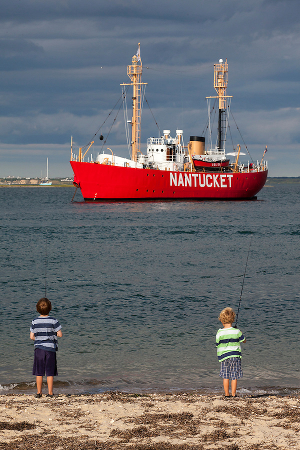 Two young boys fish at Nantucket's Brant Point Lighthouse.  In the background is Nantucket's Lightship which also helps steer boats safely into and out of Nantucket's harbor.