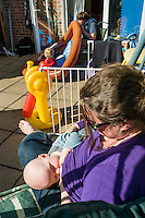 A mother breastfeeds her baby while sitting in her garden swing seat. Her husband is with their older toddler blowing up a garden pool.<br /> <br /> Taken - 27/04/2011<br /> Hampshire, England, UK