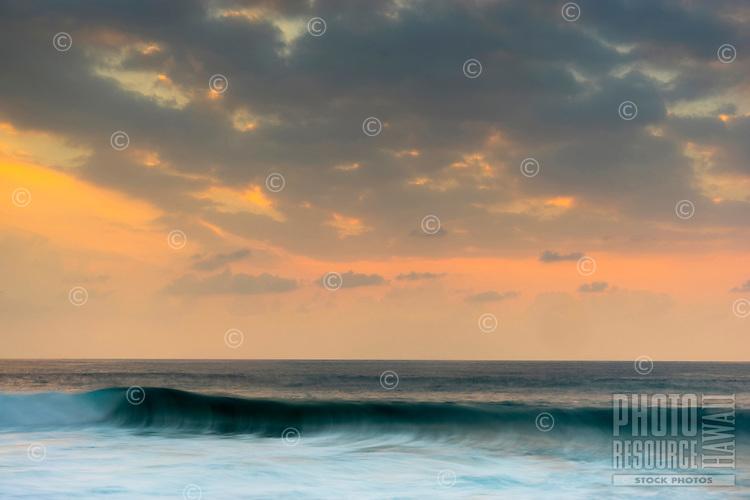 A soft golden sunset with incoming waves at Magic Sands beach, Kailua-Kona, Big Island.