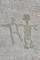 Petroglyph, rock carving, of two figure. Carved by the ancient Camunni people in the iron age between 1000-1200 BC. Rock no 24, Foppi di Nadro, Riserva Naturale Incisioni Rupestri di Ceto, Cimbergo e Paspardo, Capo di Ponti, Valcamonica (Val Camonica), Lombardy plain, Italy