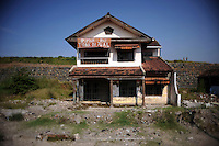 "Deserted house with the earthen dam holding back millions of gallons of mud right behind it. The banner reads defiantly: ""This house is not for sale"". Since May 2006, more than 10,000 people in the Porong subdistrict of Sidoarjo have been displaced by hot mud flowing from a natural gas well that was being drilled by the oil company Lapindo Brantas. The torrent of mud - up to 125,000 cubic metres per day - continued to flow three years later."