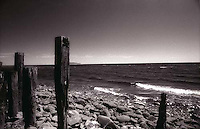 Remnants of old pier on rocky beach<br />