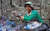 This women collecting the trash and plastic water bottles left behind by Tourists at the Bayon Temple Ruins. Siem Reap, Cambodia