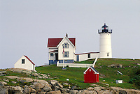 Nubble Point Lighthouse; keeper's home and red utility building; motionless flag. Coastal Maine, New England. Cape Neddick Maine.